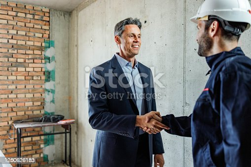 961745166 istock photo Happy building contractor and worker came to an agreement at construction site. 1250626183