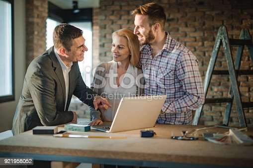 istock Happy building contractor and young couple communicating while using computer at construction site. 921958052