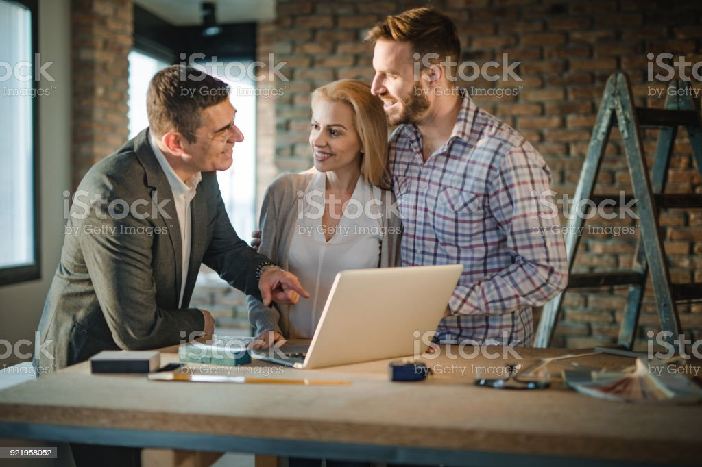 Happy building contractor and young couple communicating while using computer at construction site. stock photo