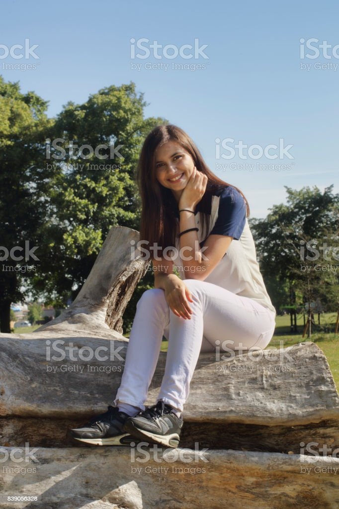Happy Bulgarian outdoor girl smiling seated on log stock photo