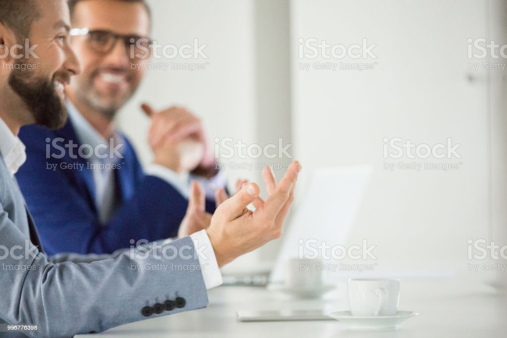 Happy business associates during meeting Businessman having a casual discussion with team in meeting. Happy business associates during meeting. Adult Stock Photo