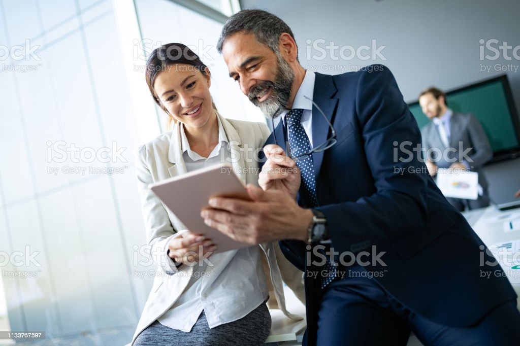 Happy business colleagues in modern office using tablet - Foto stock royalty-free di Adulto
