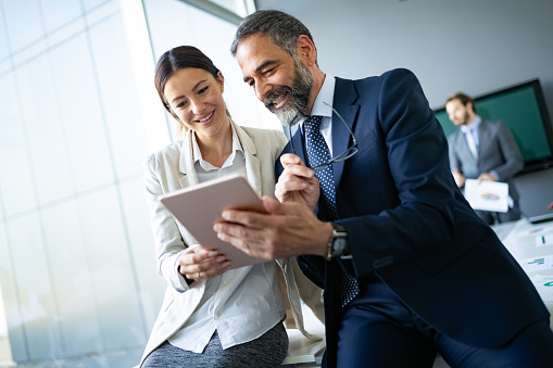 istock Happy business colleagues in modern office using tablet 1133767597