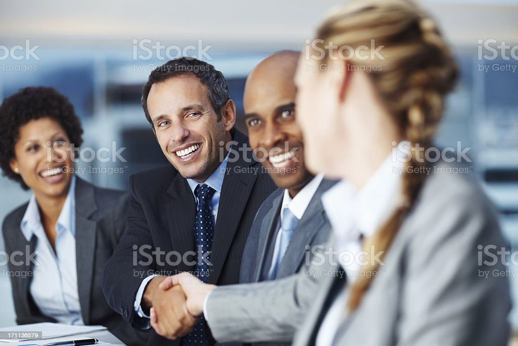 Happy business colleagues shaking hands stock photo