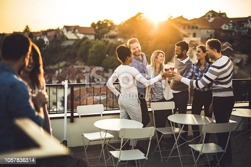 Large group of happy business colleagues having fun while toasting with their drinks on a terrace party at sunset.