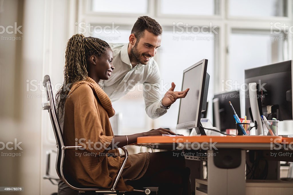 Happy business colleagues working on PC at corporate office. stock photo