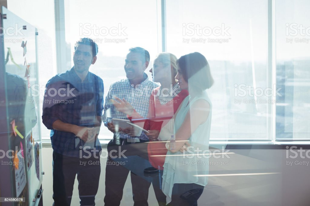 Happy business entrepreneurs looking at whiteboard seen through glass stock photo