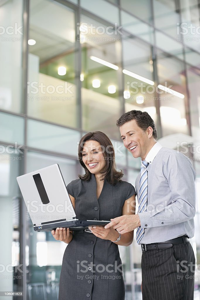 Happy business executives standing with laptop in modern office building royalty-free stock photo