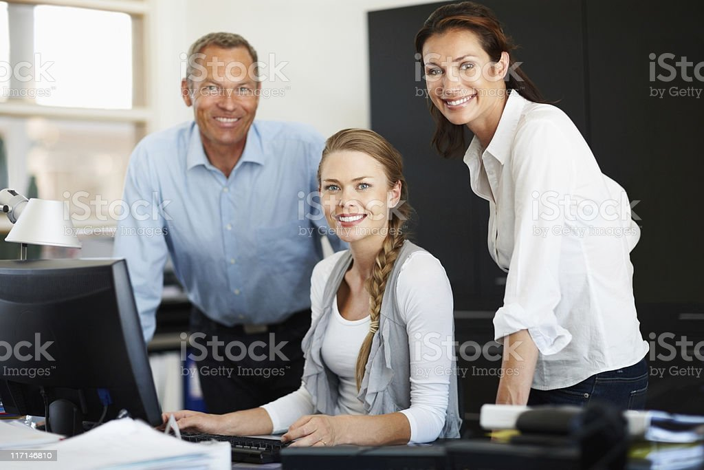 Happy business executives with computer giving you a warm smile royalty-free stock photo