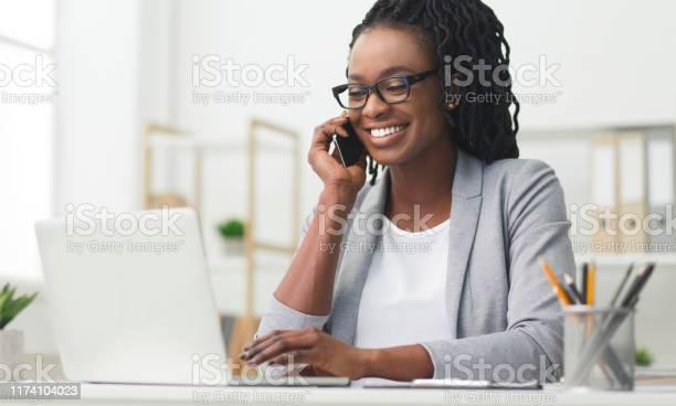 Happy business girl having phone conversation using laptop in office picture id1174104023?b=1&k=6&m=1174104023&s=612x612&h=t42avdhpt j7wujz6zpcc2 80pkjy2rgvlba1171t7m=