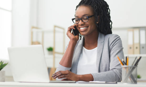 happy business girl having phone conversation using laptop in office - business woman foto e immagini stock