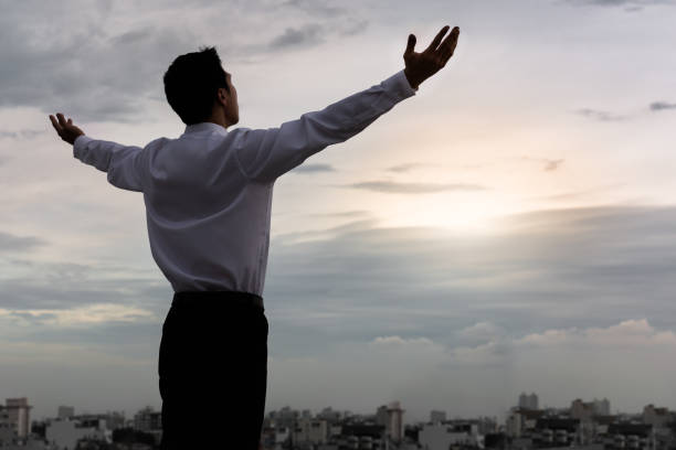 Happy business man beginning his day inspired. A man standing in front of the city sunrise with his arms lifted with hope and thankfulness. fresh start morning stock pictures, royalty-free photos & images