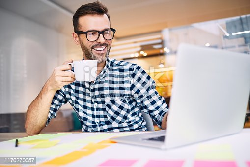 Happy business man drinking coffee working on his laptop from home office