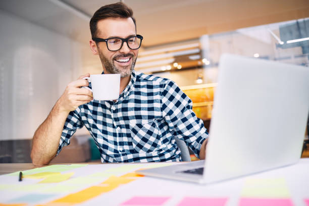Happy business man drinking coffee working on his laptop from home office stock photo
