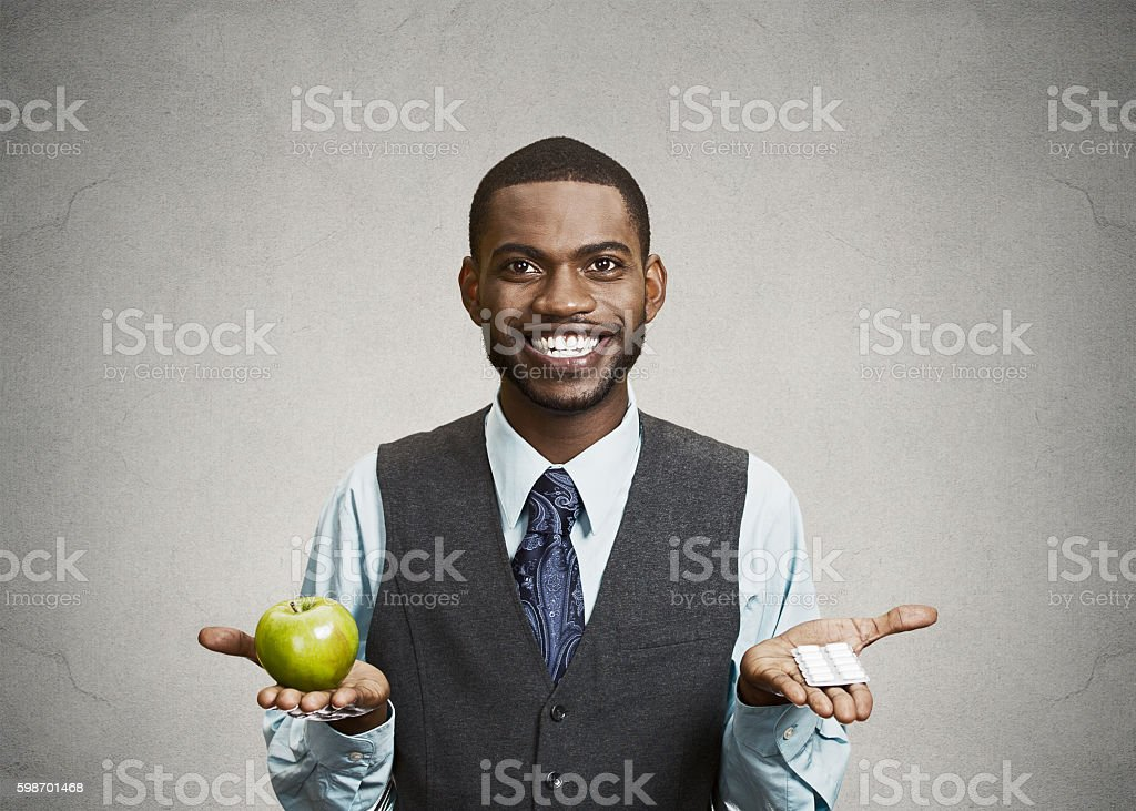 Happy business man holds green apple and pills stock photo