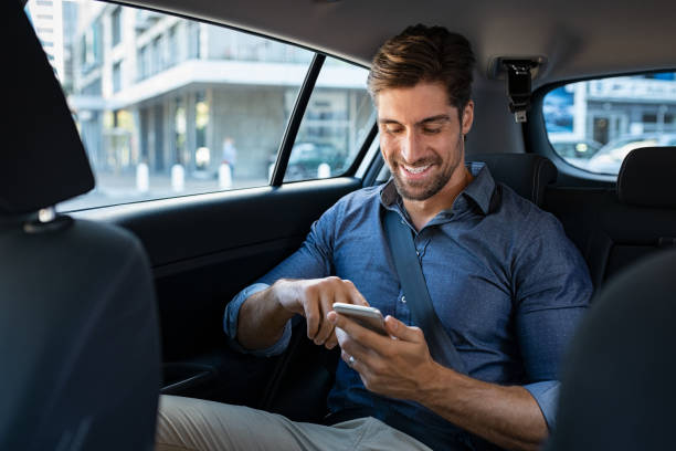 Happy business man in car using phone Happy smiling businessman man typing message on phone while sitting in a taxi. Young businessman in formal clothing using smartphone while sitting on back seat in car. Cheerful guy messaging wirth cellphone. passenger stock pictures, royalty-free photos & images