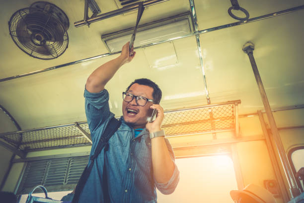 happy business man of tourist talking smartphone and holding hand grip of train for journey and travel - hand grip stock photos and pictures