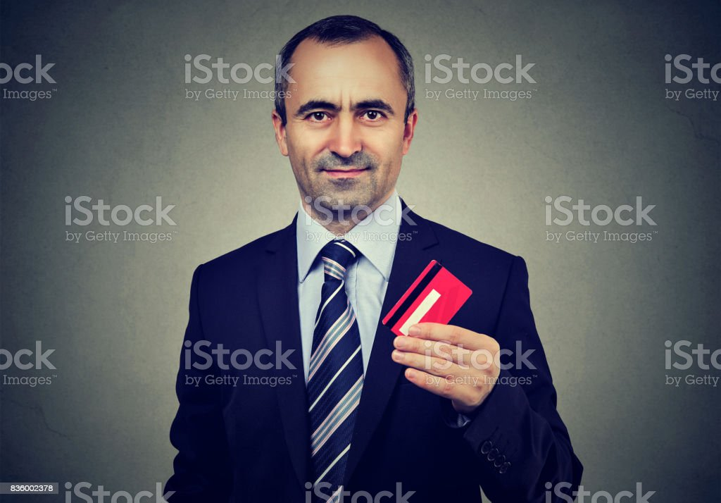 Happy business man offering new credit card stock photo