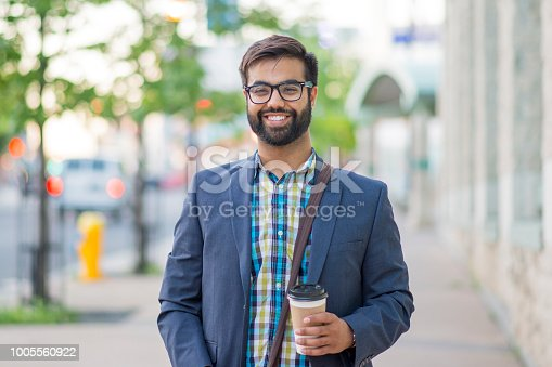 Handsome Indian business man walking leisurely in an urban city area holding a cup of coffee and wearing a shoulder bag. He is smiling and wearing a collared shirt and blazer.