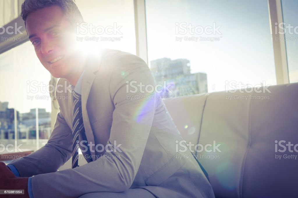 Happy business man sitting on sofa and looking at camera stock photo