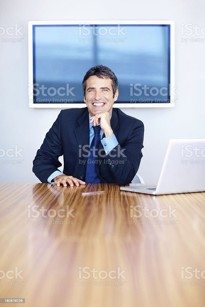 Happy business man sitting with hand on chin royalty-free stock photo