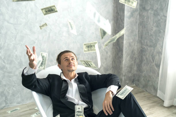 Happy business man very rich guy throw money dollar bills in air like rain money bill and banknotes US dollar bill on the bathtub - business success concept stock photo