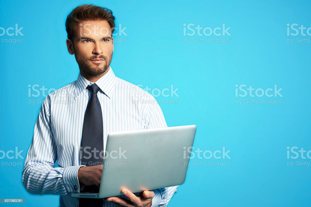 Happy business man with a laptop Successful man isolated over a blue background 2015 Stock Photo