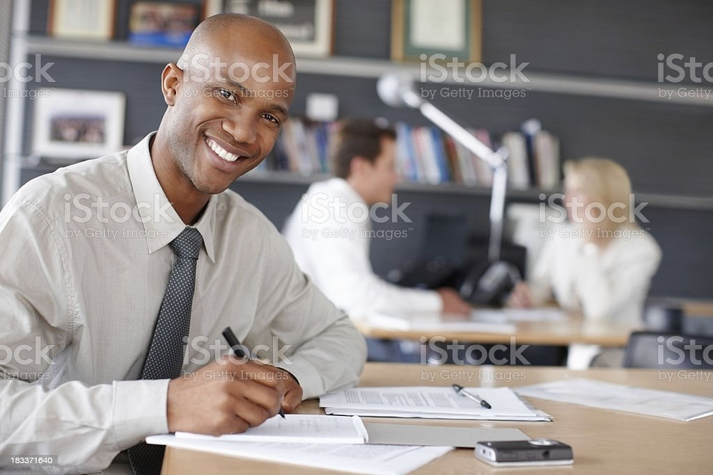 Happy business man with colleagues in the background stock photo