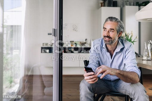 istock happy business man with mobile ilooking out of window 1147503275