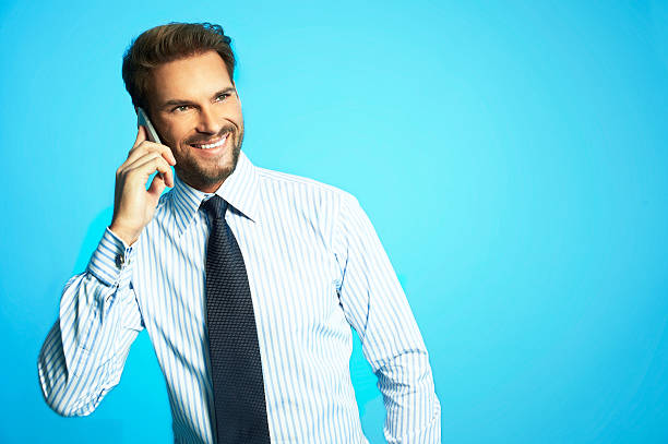 Happy business man with phone, isolated over blue background stock photo