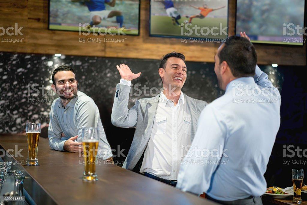 Happy business men having drinks at the bar - foto de acervo