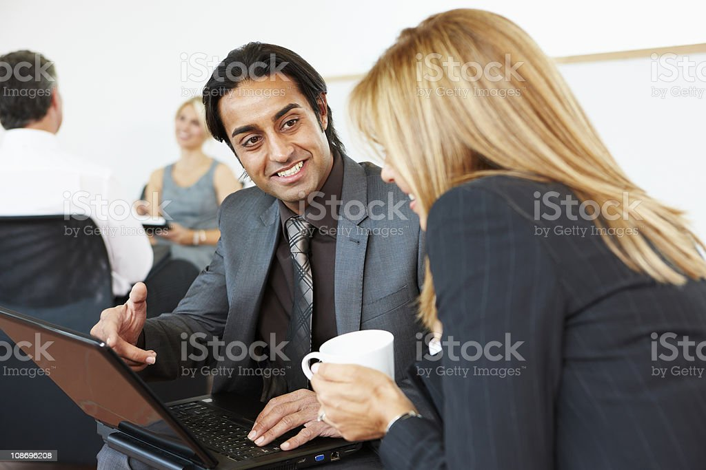 Happy Business mentor looking at laptop with client royalty-free stock photo