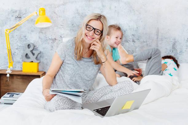 Glückliche Unternehmen Mama bei der Arbeit, während ihre Kinder im Bett spielen und Spaß haben – Foto