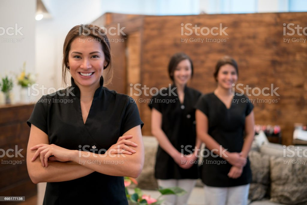Happy business owner at a spa with a group of workers stock photo