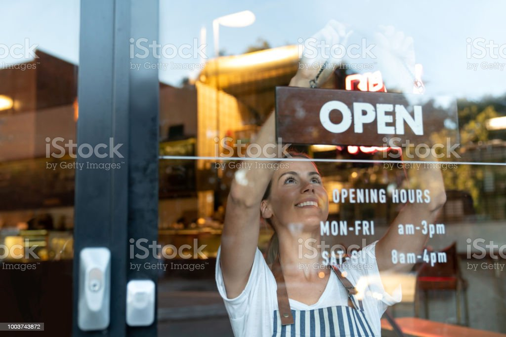 Happy business owner hanging an open sign at a cafe Portrait of a happy business owner hanging an open sign on the door at a cafe and smiling - food and drinks concepts 20-29 Years Stock Photo
