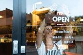 幸せなビジネスの所有者がカフェでオープン サインをぶら下げ