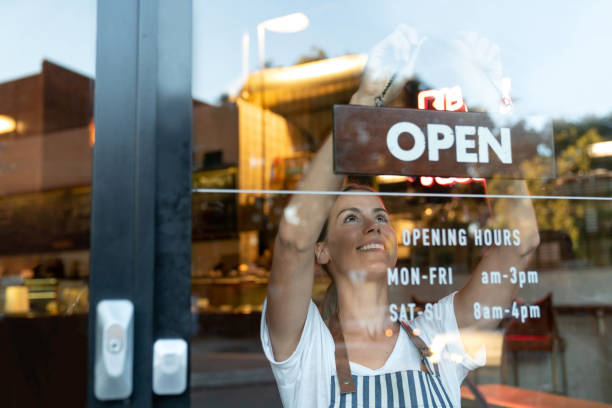 happy business owner hanging an open sign at a cafe - panetteria foto e immagini stock
