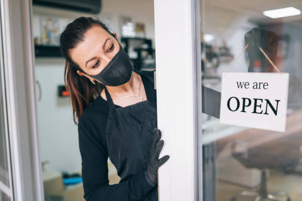 happy business owner hanging an open sign during covid-19 - small business owner stock pictures, royalty-free photos & images