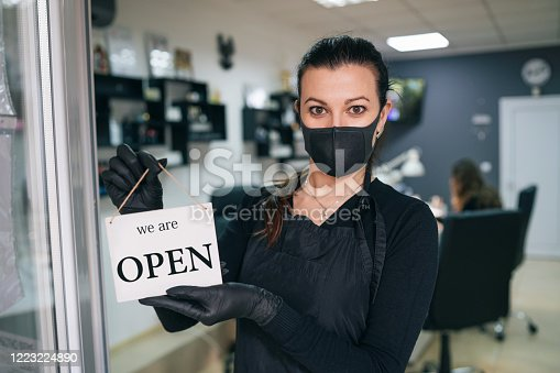 Happy business owner hanging an open sign during COVID-19
