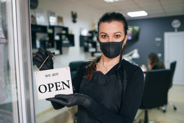 Happy business owner hanging an open sign during COVID-19 stock photo