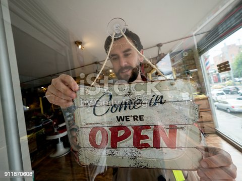 Portrait of a happy business owner hanging an open sign on the door at a barber shop