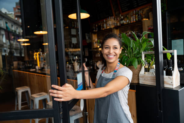 happy business owner opening the door at a cafe - owner stock pictures, royalty-free photos & images