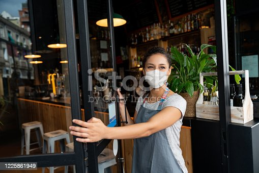 istock Happy business owner opening the door at a cafe wearing a facemask 1225861949