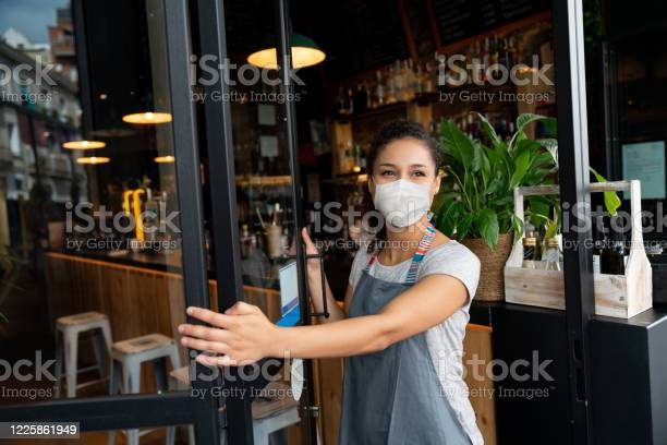 Happy business owner opening the door at a cafe wearing a facemask picture id1225861949?b=1&k=6&m=1225861949&s=612x612&h=u21ddufsmhwxndkmi3kqe4hkrctltwiwt3b2o8nbj9a=