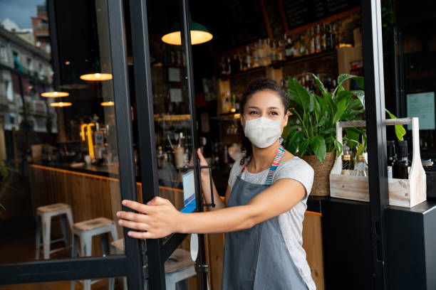 happy business owner opening the door at a cafe wearing a facemask - máscaras imagens e fotografias de stock