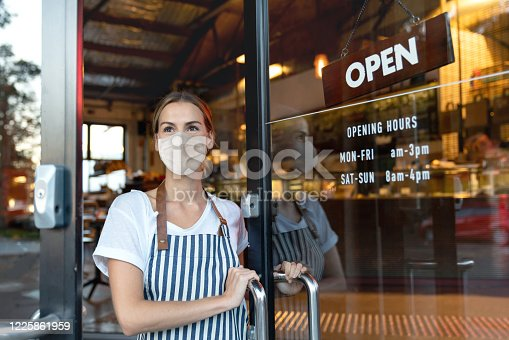 istock Happy business owner opening the door at a cafe wearing a facemask 1225861959