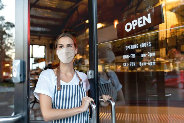 glücklicher geschäftsinhaber öffnet die tür eines cafés mit einer gesichtsmaske - offen allgemeine beschaffenheit stock-fotos und bilder