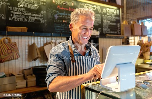 istock Happy business owner placing an order on the computer at a cafe 1003743986