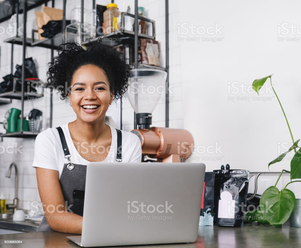 Happy business owner standing at counter with her laptop stock photo