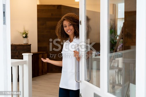 Portrait of a happy business owner working at a spa and opening the door smiling - lifestyle concepts